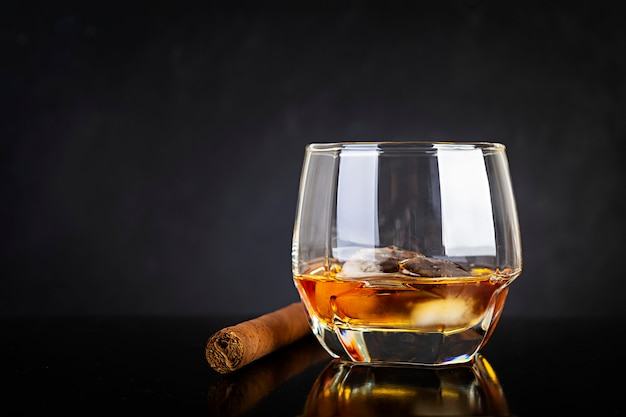 Стекло вискиа и сигары на темной предпосылке.