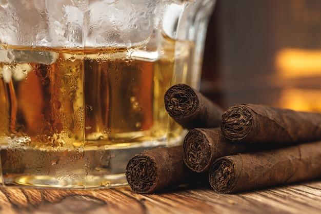 Стакан виски и скрученных сигар на деревянном столе крупным планом
