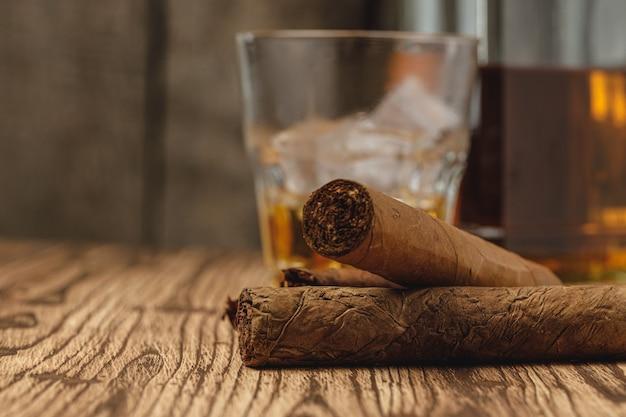 ウイスキーと葉巻の木製のテーブルのガラス