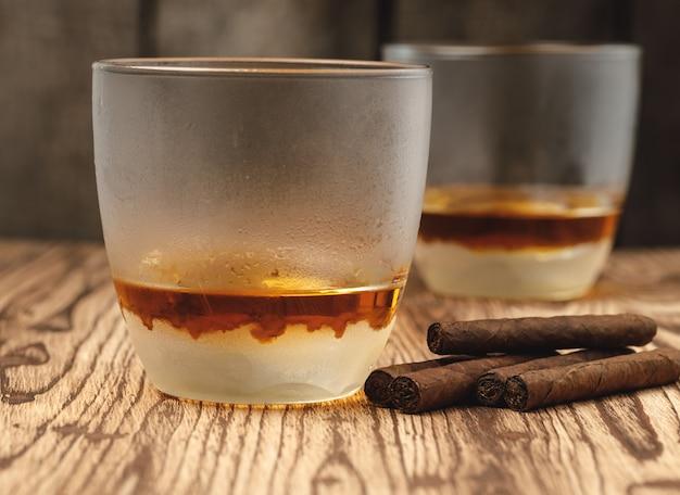 Стакан виски и скрученных сигар на деревянном столе