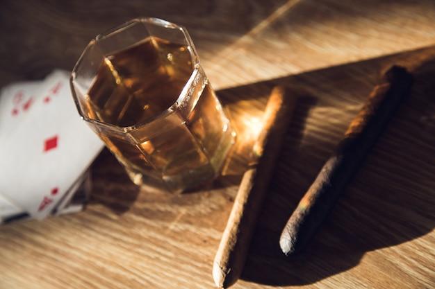 Стакан виски, сигары и карт на столе