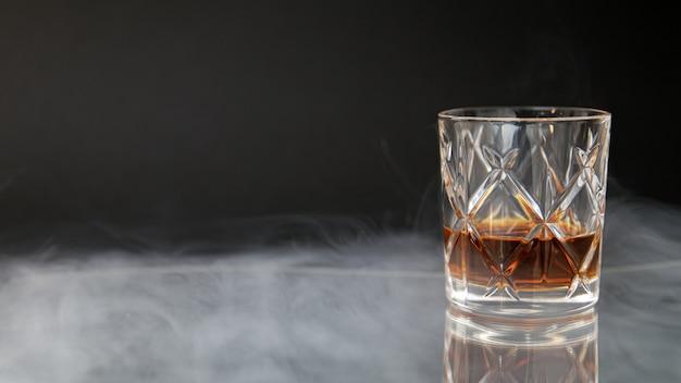 黒の背景に煙に囲まれたテーブルにウイスキーのグラス