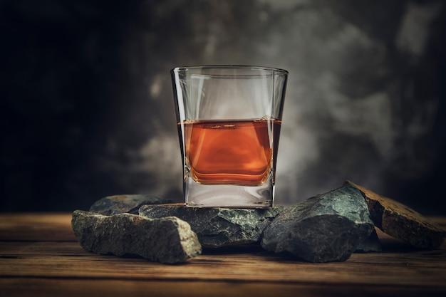 暗い石の上のウイスキーのガラス