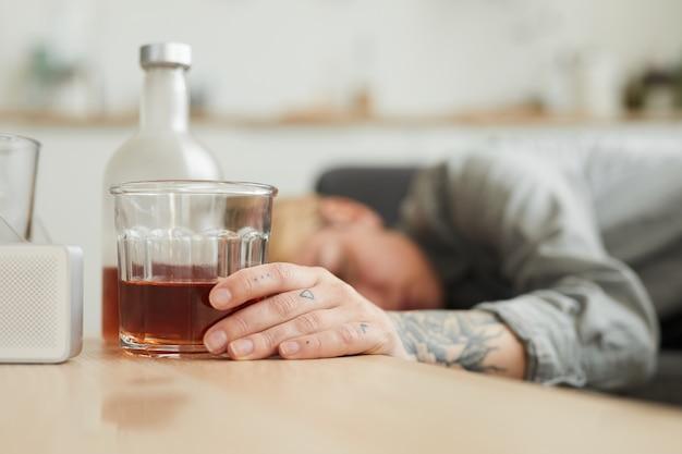 彼女は自宅のキッチンにいるバックグラウンドで寝ている女性とテーブルの上のウイスキーのガラス