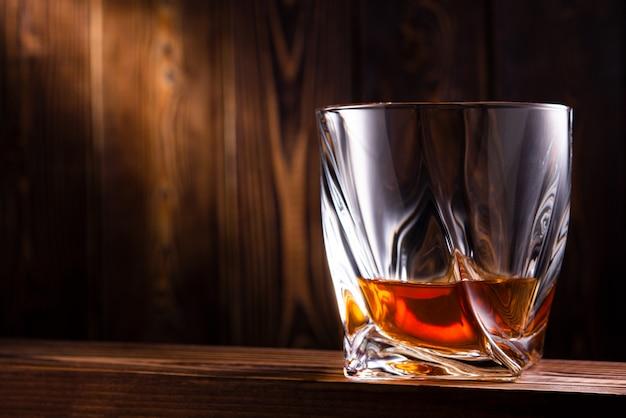 Стакан виски или коньяка на деревянной стене
