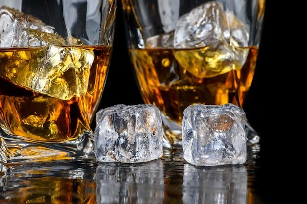 黒の背景にキューブアイスとウイスキーまたは他のアルコールのガラス