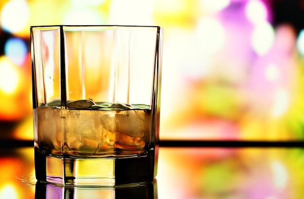 カラフルな背景の上のウイスキーのガラス