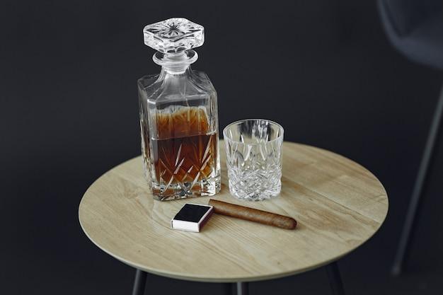 テーブルの上の葉巻とウイスキーのガラス。アルコールと葉巻の写真をクローズアップ。