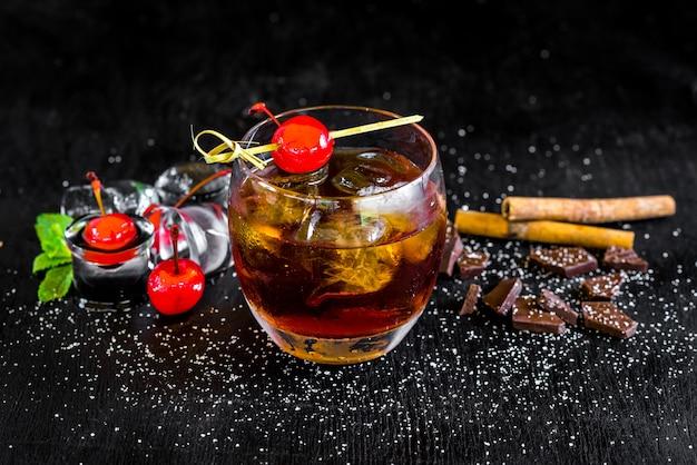 氷と黒の背景にチェリーとウイスキーのガラス