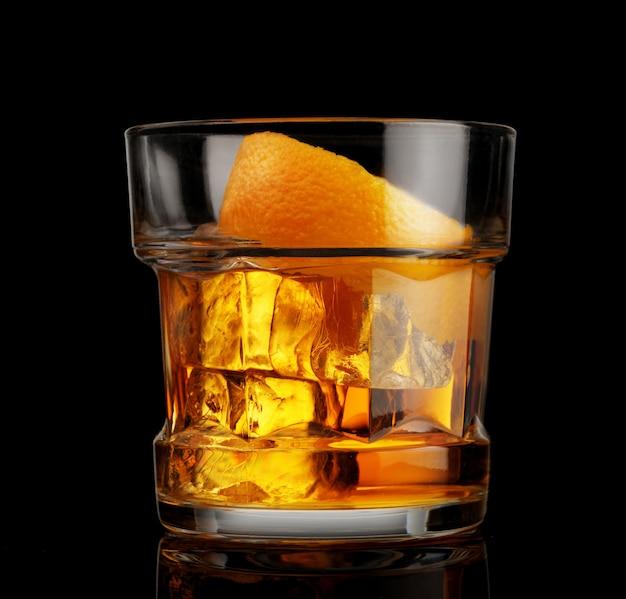 黒の背景に氷とオレンジの皮とウイスキーのガラス