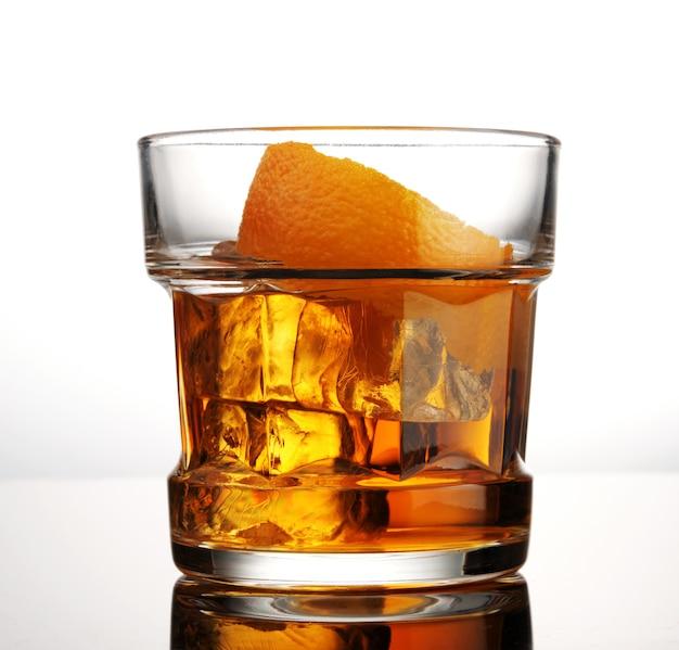 白い背景の上の氷とオレンジの皮とウイスキーのガラス