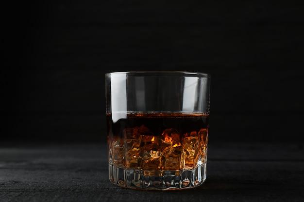 Стакан виски с кубиками льда на фоне темных деревянных, место для текста