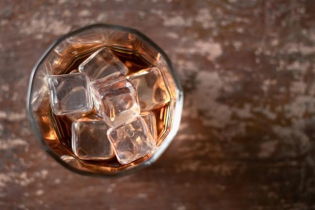 黒の背景に氷とウィスキーのガラス
