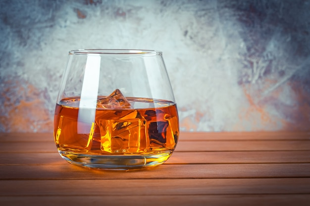氷とウイスキーのグラス。静物。茶色の木製テーブルにブランデー、バーボン。強いアルコール飲料。ラム酒、スコッチ。テキスト用のスペースをコピーします。