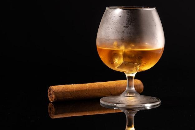 黒の背景にウイスキーと葉巻のガラスをクローズアップ