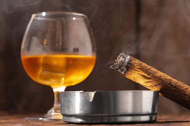 Стакан виски и зажженная сигара в пепельнице на деревянном фоне