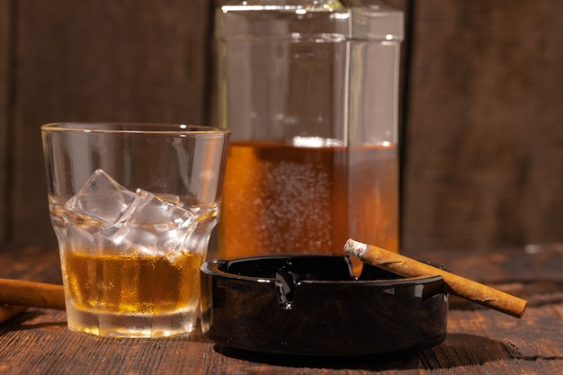 Стакан виски и зажженная сигара в пепельнице