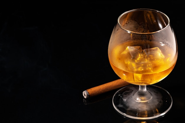 黒の背景にウイスキーと火のついた葉巻のガラスをクローズアップ