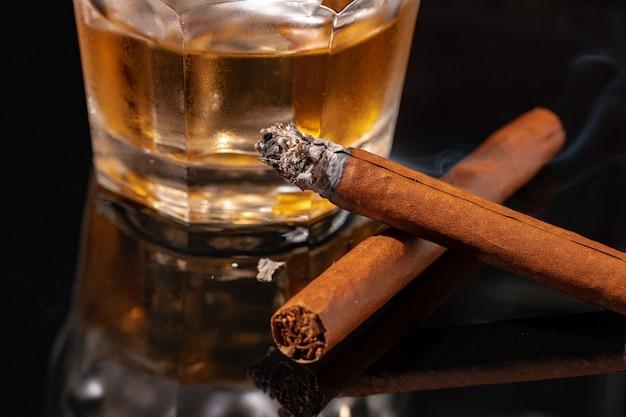 Стакан виски и зажженная сигара на черном фоне