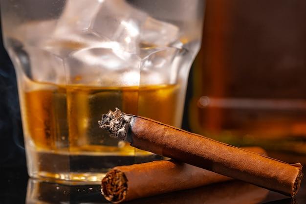 黒の背景にウイスキーと火のついた葉巻のガラス