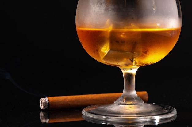黒い表面にウイスキーと火のついた葉巻のガラス