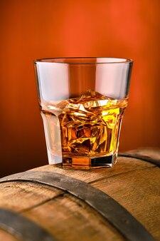 Стакан виски со льдом на верхней части бочки
