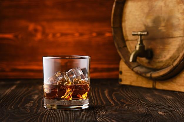 背景にバレルと氷とウイスキーのガラス