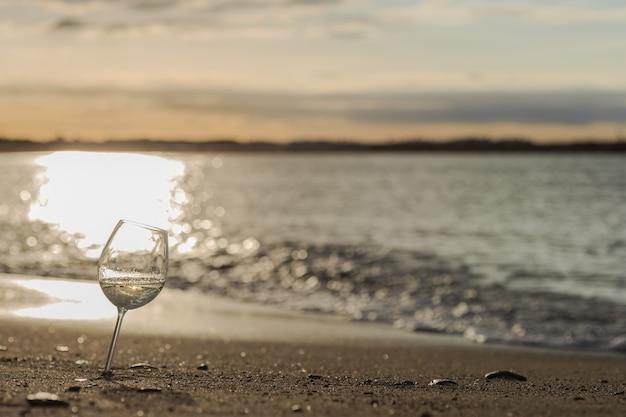 日没時のビーチで白ワインのグラス