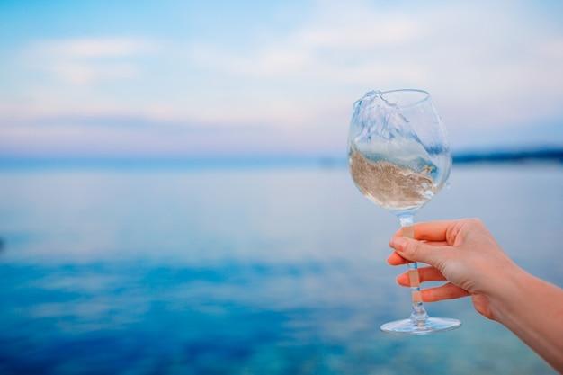 夕日の熱帯のビーチで白ワインのグラス