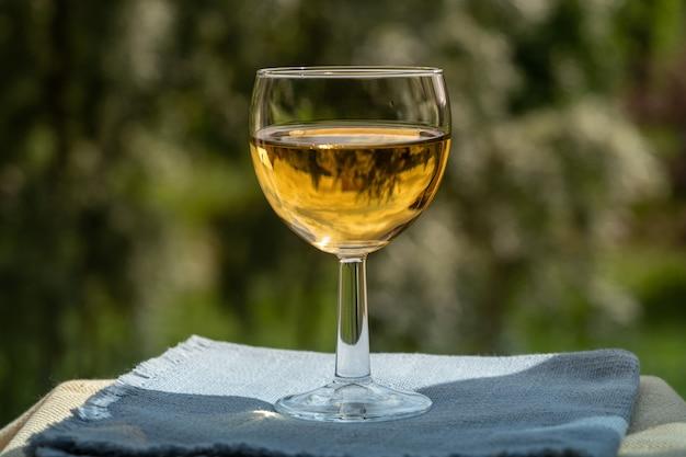 Бокал белого вина на фоне зеленого сада.