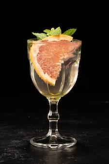 黒の背景にグレープフルーツスライスとミントの葉と白ワインサングリアのガラス