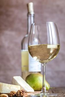 Стакан белого вина с сыром и орехами