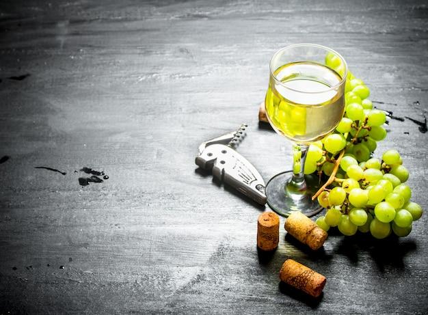 코르크와 흰 포도의 무리와 함께 화이트 와인의 유리.