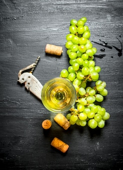 コルクと白ブドウの束と白ワインのグラス。