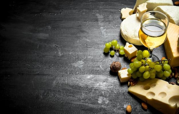 さまざまなチーズ、ブドウ、ナッツと白ワインのグラス。黒い木製のテーブルに。