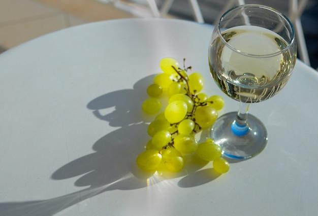 햇빛이 비치는 발코니 테라스에서 흰색 테이블에 포도를 넣은 화이트 와인 한 잔