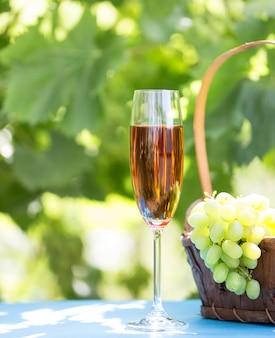 グラスにワインとブドウの房のバスケット