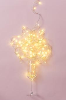 ピンクの背景の最小限の創造的なパーティーのコンセプトに電球とワインと花輪のガラス。