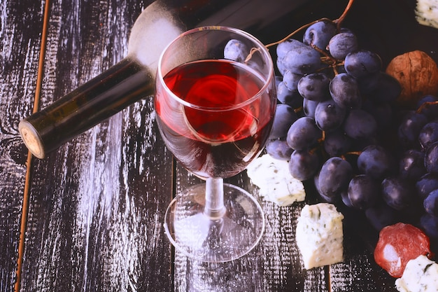 Стакан вина, виноград, алкоголь, бутылка, сыр, изношенный, деревянный фон, ретро, винтажный стиль.