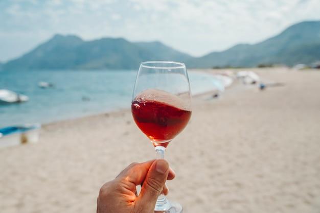 Бокал вина в руке бокал красного вина на фоне средиземноморского пляжа