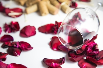 Glass of wine on the table with rose petals