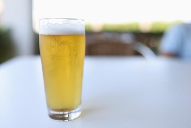 Наливается стакан желтого холодного пива с белой пеной.