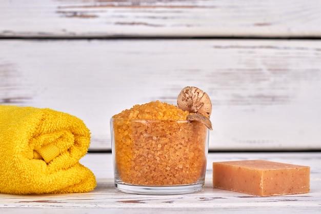 압연 수건과 수제 비누가 있는 노란색 소금 한 잔.