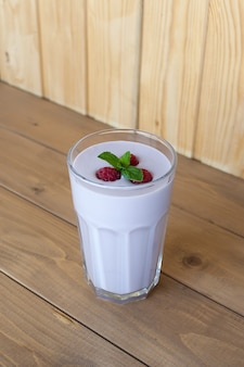 Стакан йогуртового коктейля, смузи с малиной стоит на березовом пне на деревянном столе