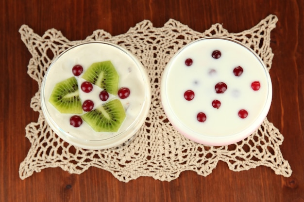 木製の背景に、フルーツとベリーのヨーグルトデザートのガラス