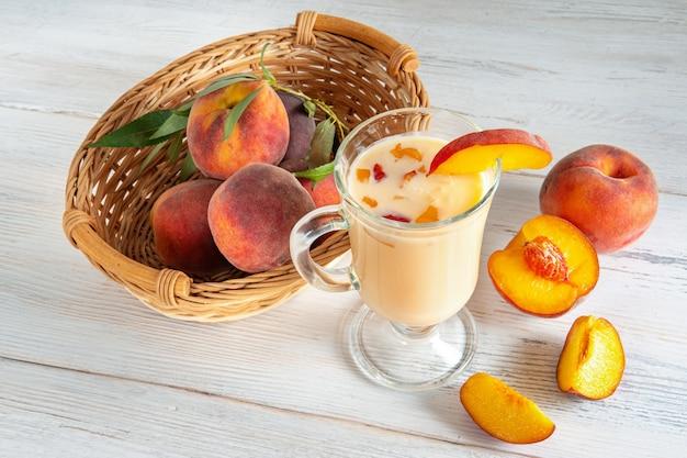 잘 익은 달콤한 과일 조각이 든 요구르트 한 잔, 배경에 바구니에 녹색 잎이 있는 복숭아
