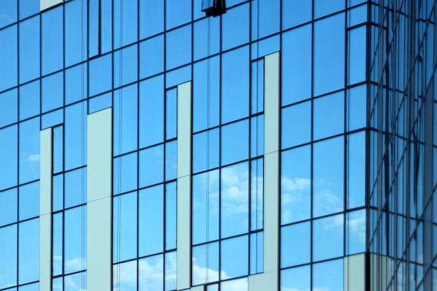 Glass office building, view of the sky reflected in the windows.
