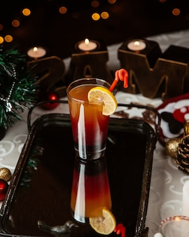 A glass of ombre cocktail garnished with lemon slice around christmas decorations