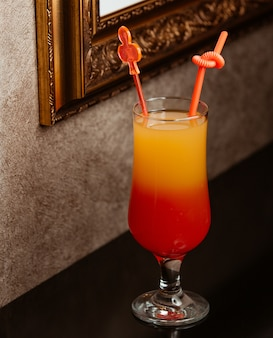 A glass of ombre cocktail with plastic straw and cocktail stirrer