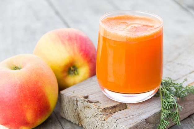 Glass of orange carrot juice with apples on wood